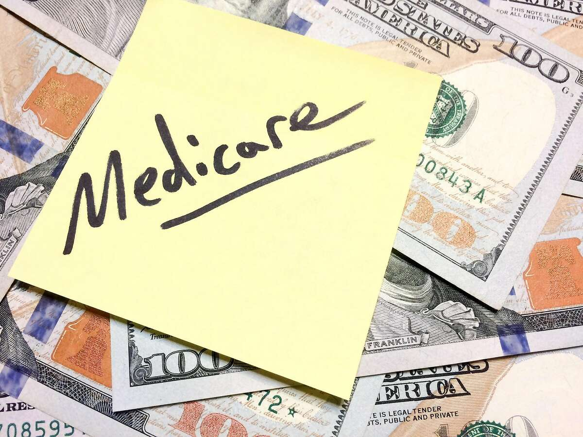 American cash money and yellow sticky note with text Medicare in black color aerial view