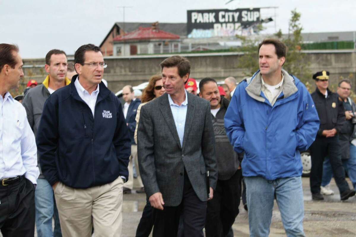 Jim Torgerson, chief executive officer of Avangrid, walks with then-Governor Dannel Malloy during an undated event in Bridgeport. Torgerson retired from his position on Tuesday.