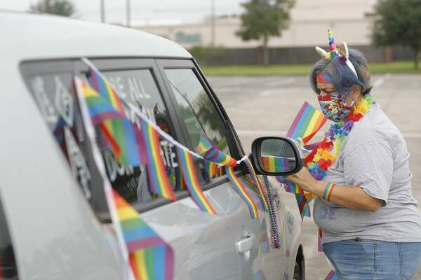 Candida Garcia decorates her car during a car parade hosted by There's Room at our Table in honor of PRIDE month at Woodforest Bank Stadium, Saturday, June 27, 2020, in Shenandoah. The newly formed group aims to bring allies and LGBTQ+ people together.