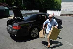 Paolo Martino, of New Milford, carries his recycling from his car at the New Milford Recycling Center on June 26.