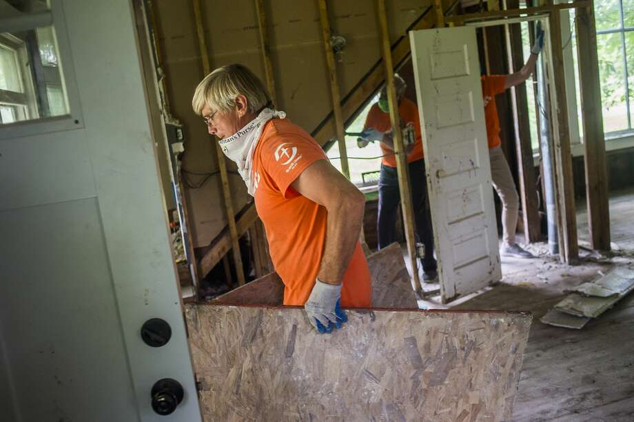 Kurt Weinberger, a volunteer with Samaritan's Purse, removes sheets of plywood from a home on E. Pine River Road as his crew wraps up their efforts Friday, June 26, 2020 in Midland. Over the course of five weeks, the organization has employed the assistance of 1,500 volunteers to aid over 300 area families with flood relief. (Katy Kildee/kkildee@mdn.net) Photo: (Katy Kildee/kkildee@mdn.net)