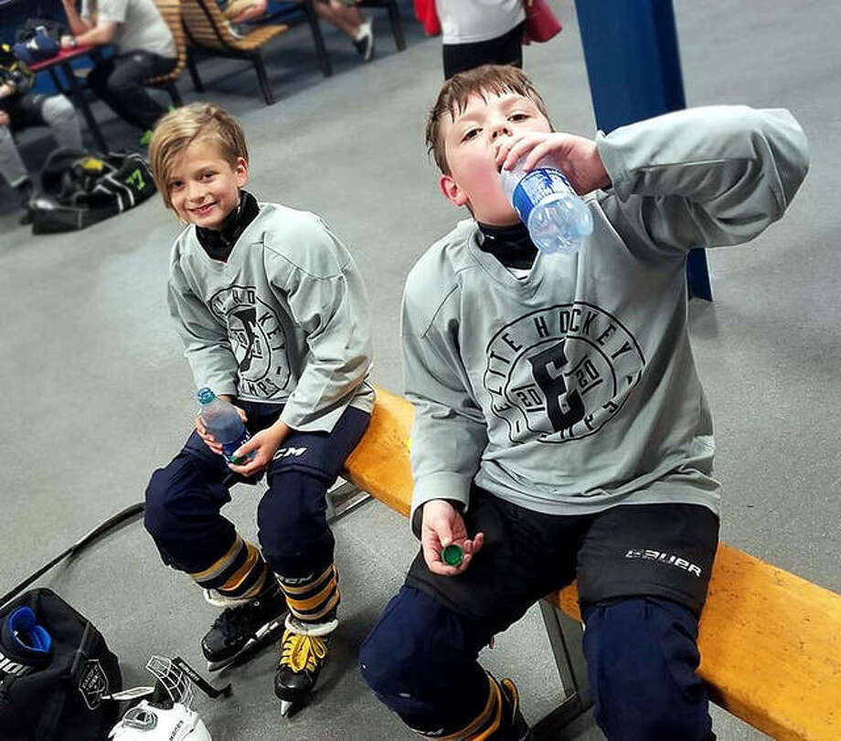 Gavin Schmitt, right, takes a drink as he and Cooper Hicks rest up following a session of their Elite Hockey training session Saturday at the East Alton Ice Arena, which has reopened with restrictions following shutdown in March because of the COVID-19 pandemic. Photo: Cale Schmitt Submitted Photo