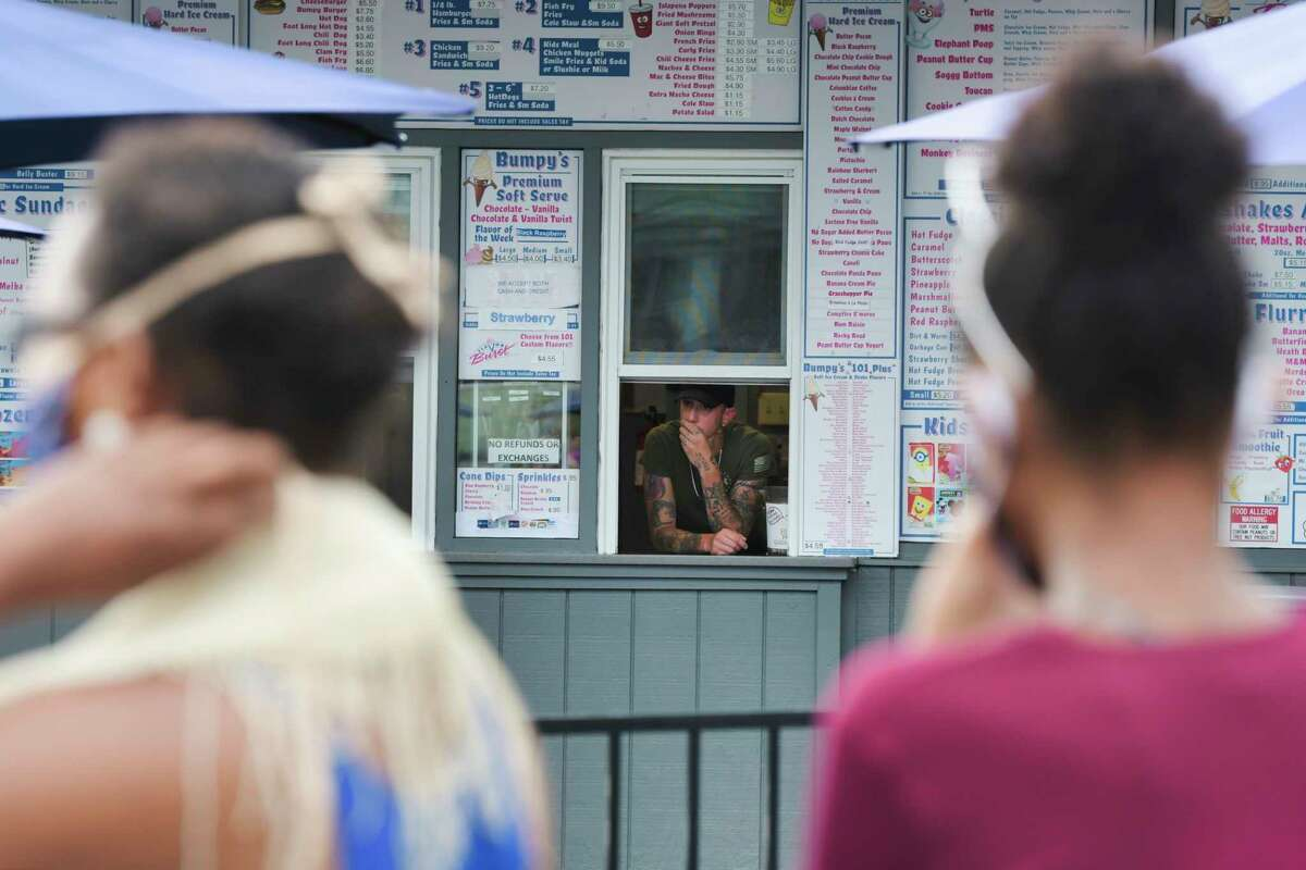 A employee looks out the counter window as protesters gather in front of Bumpy's Polar Freeze on Sunday, June 28, 2020, in Schenectady, N.Y. The protest at the business was organized after what is alleged to be the owner's racist texts that had been leaked. (Paul Buckowski/Times Union)