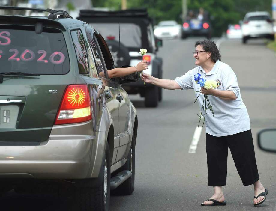 Annarose Russo hands out carnations to East Haven High School grads in a motorcade starting out at Coe Avenue and ending at East Haven High School on June 28, 2020. Photo: Arnold Gold, Hearst Connecticut Media / New Haven Register