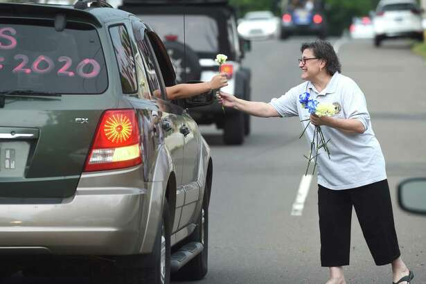 Annarose Russo hands out carnations to East Haven High School grads in a motorcade starting out at Coe Avenue and ending at East Haven High School on June 28, 2020.