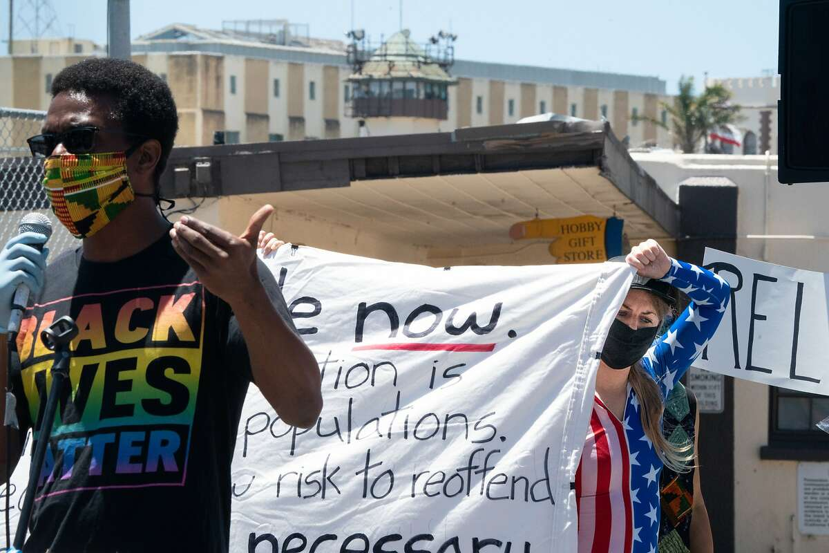 Speaker Emile DeWeaver, left, speaks as Jessica McKellar, right, helps holds a banner at the Stop San Quentin Outbreak rally at the prison gates on Sunday, June 28, 2020 in San Rafael, Calif.