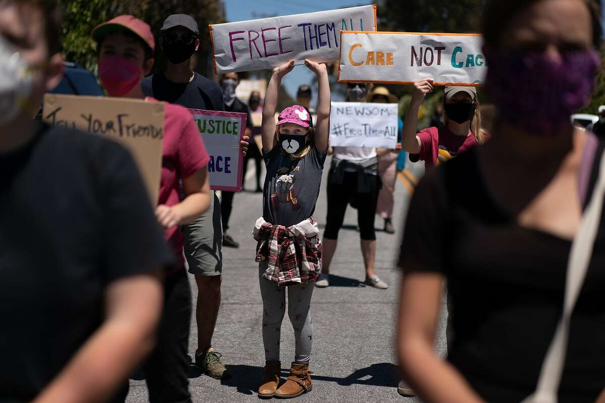 Bridget Schwartz, 12, center, holds a banner at the Stop San Quentin Outbreak rally at the prison gates on Sunday, June 28, 2020 in San Rafael, Calif. The group is concerned about he safety of the inmates being exposed to the coronavirus.