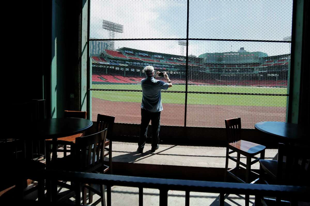 In this June 25, 2020, photo, a reporter photographs the view of the baseball field at Fenway Park from the Bleacher Bar in Boston. Tucked under the center field seats at Fenway Park, down some stairs from Lansdowne Street in an area previously used as the visiting teama€™s batting cage, is a sports bar that is preparing to reopen from the coronavirus shutdown. If Major League Baseballa€™s plans remain on schedule, it may be one of the few places fans will be able to watch a game in person this season. (AP Photo/Elise Amendola)