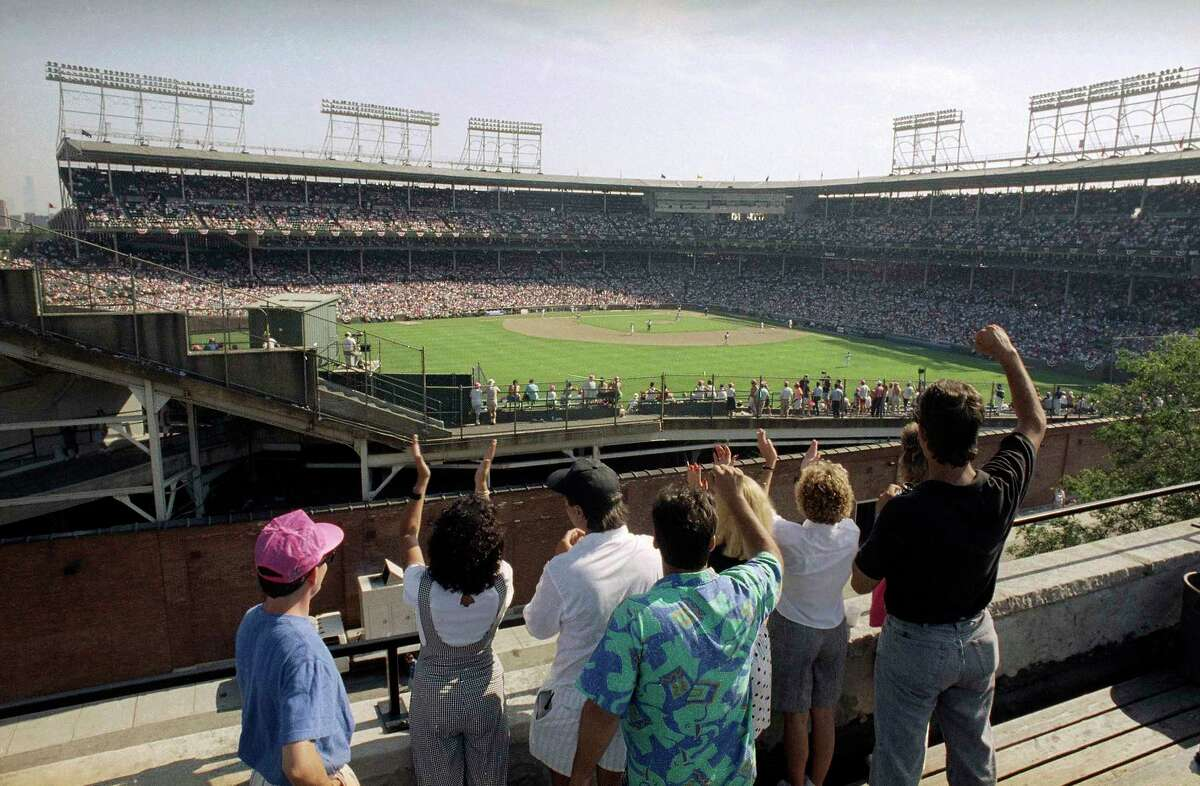 FILE - In this Monday, July 9, 1990, file photo, spectators watch an All-Star Game practice session from the roof of a building just outside Chicago's Wrigley Field. This week, Major League Baseball players and owners reached an agreement to play an abbreviated, 60-game season that would start July 23 or 24 in teamsa€™ home ballparks. But the seats will be empty. Instead, fans hoping to see a game in person will be have to settle for pressing their faces up against hotel windows, squinting through metal grates or climb to rooftops when baseball returns this month in otherwise empty stadiums. (AP Photo/Seth Perlman, File)