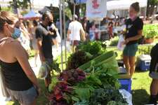 Fresh produce is spread out for purchase in Nature View Farm's booth during the opening day of the Fairfield Farmers Market on Sherman Green in Fairfield, Conn. on Sunday, June 28, 2020.