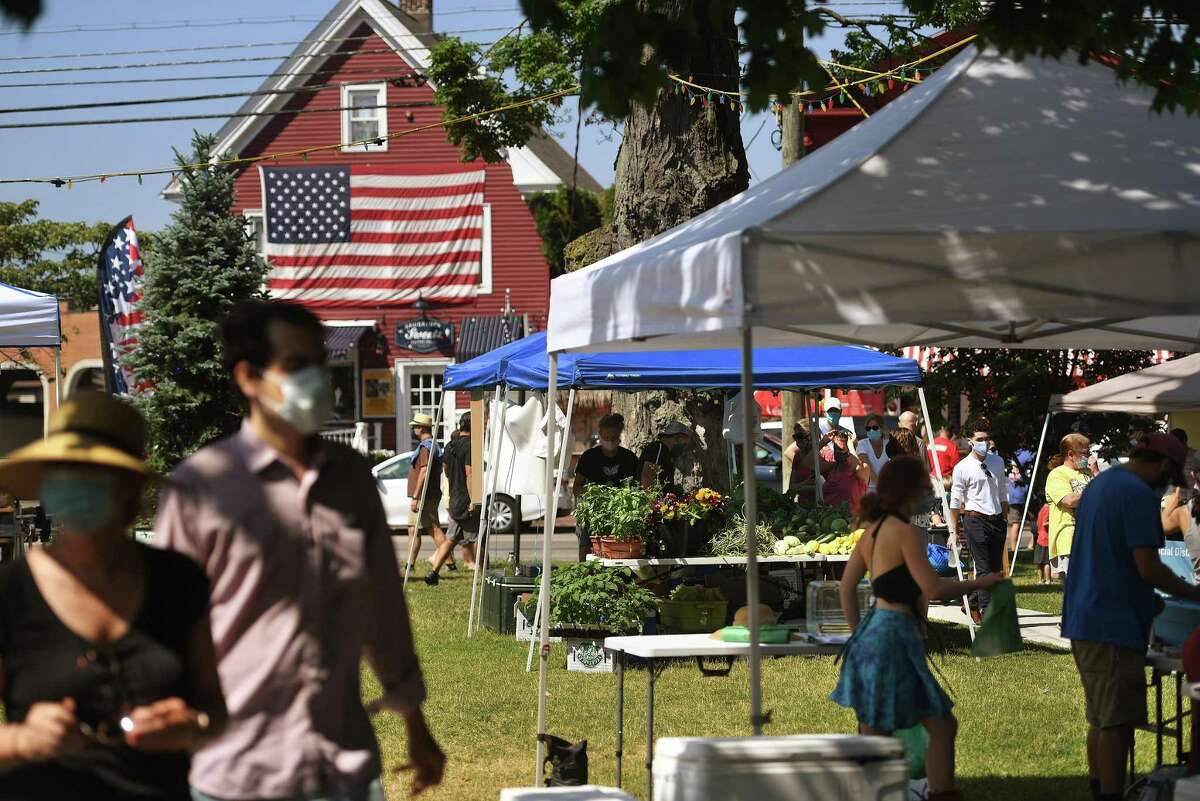 Customers shop for fresh produce on the opening day of the Fairfield Farmers Market on Sherman Green in Fairfield, Conn. on Sunday, June 28, 2020.