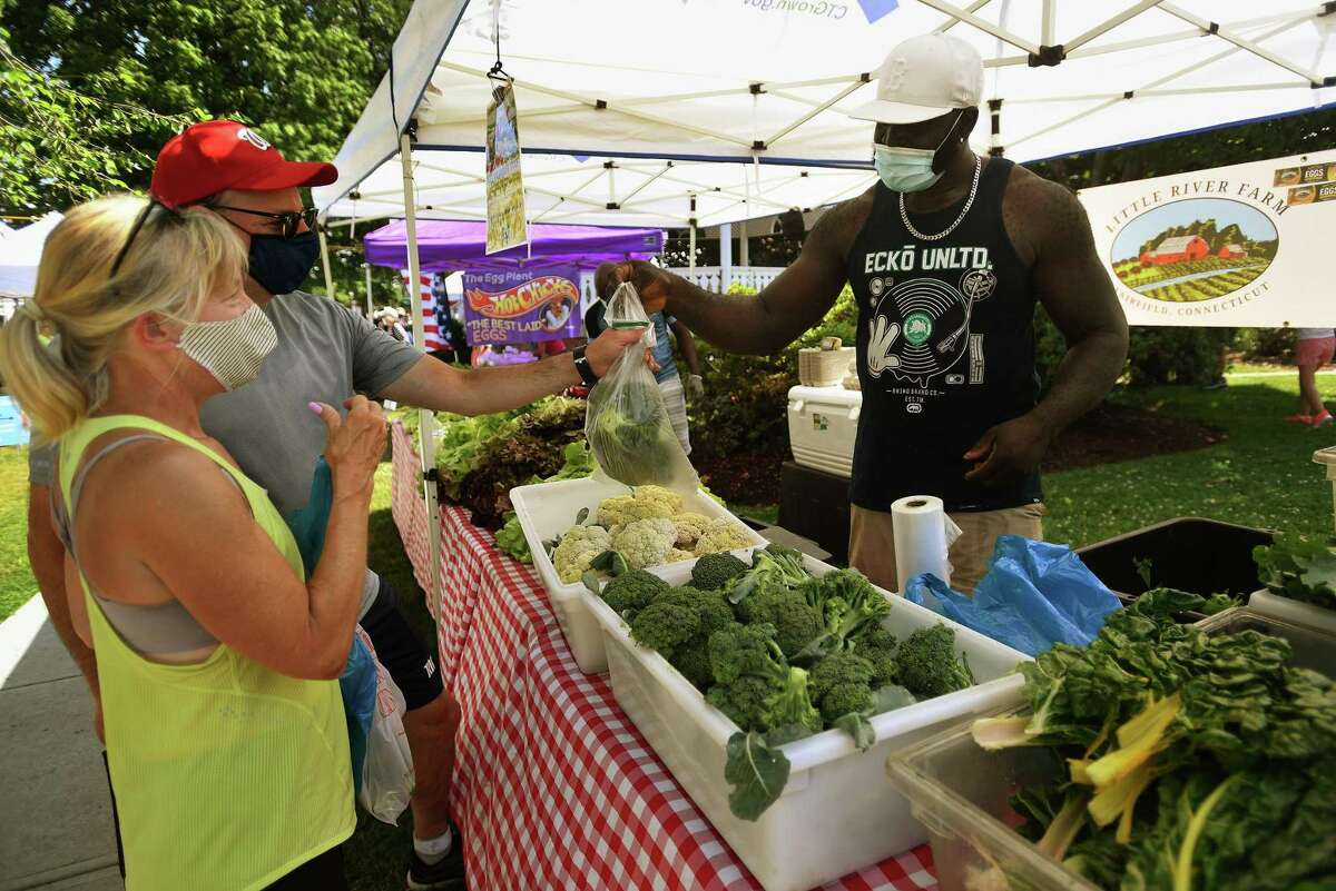 Lisa and Len Wolin, of Fairfield, purchase fresh produce from Octavious Stoddart of Little River Farm in Fairfield during the opening day of the Fairfield Farmers Market on Sherman Green on Sunday, June 28, 2020. at right, customers browse among the produce tables.