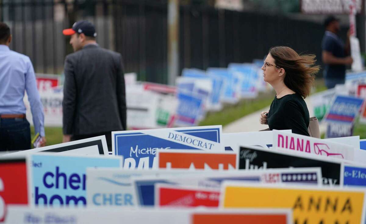 People walk by campaign signs outside the early voting location at the Metropolitan Multi-Purpose Center, 1475 W. Gray St., Tuesday, Feb. 18, 2020 in Houston.