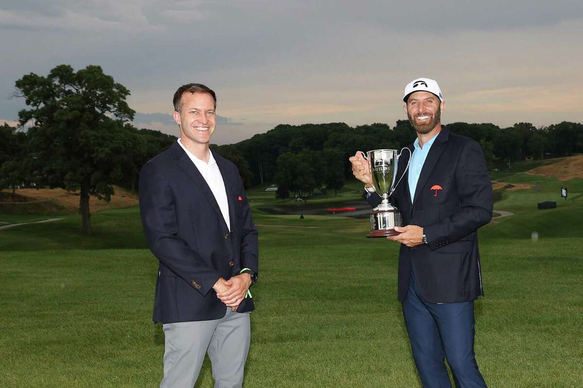 Dustin Johnson of the United States poses with the trophy after winning the Travelers Championship at TPC River Highlands on Sunday in Cromwell.