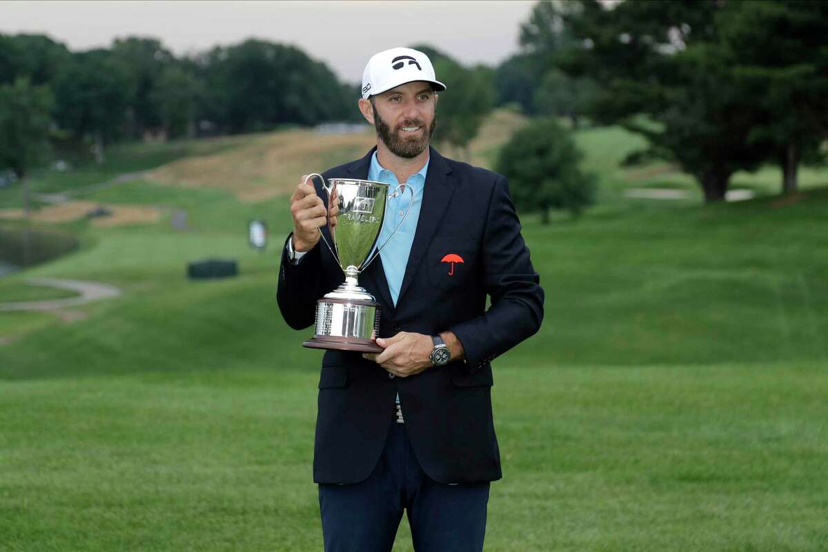 Dustin Johnson poses with the trophy after winning the Travelers Championship golf tournament at TPC River Highlands on Sunday in Cromwell.