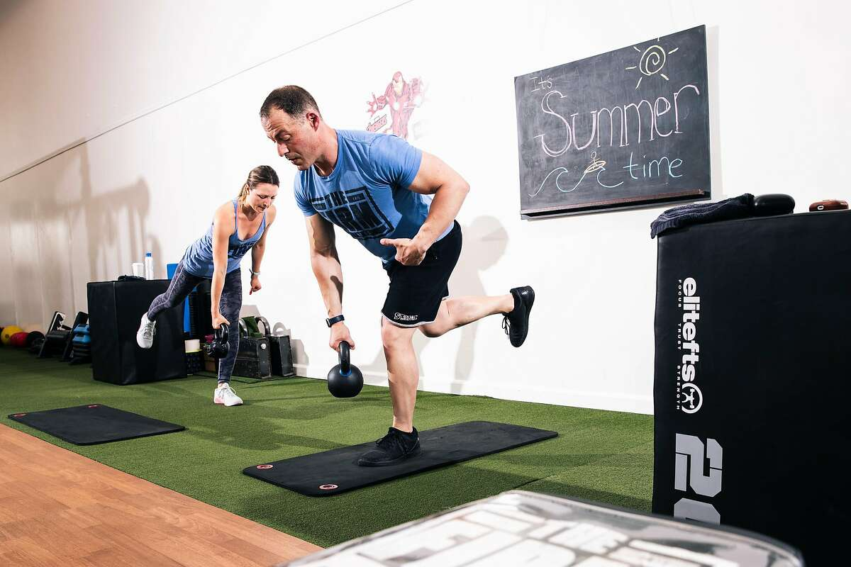 Trainer Justyna Sproull, left, and J.J. Miller, founder of The Firm Fitness, lead a fitness class over Zoom on Wednesday, June 10, 2020 in San Francisco, California.