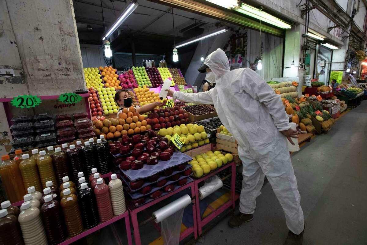 Un trabajador sanitario con equipo protector para reducir la propagación del nuevo coronavirus, provee alcohol a una vendedora para que desinfecte sus manos en el mercado conocido como Central de Abastos en la Ciudad de México, el jueves 18 de junio de 2020.