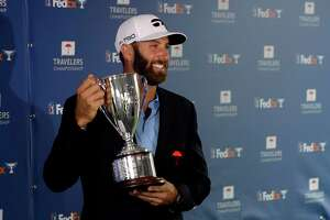 Dustin Johnson poses with the trophy after winning the Travelers Championship Sunday in Cromwell.