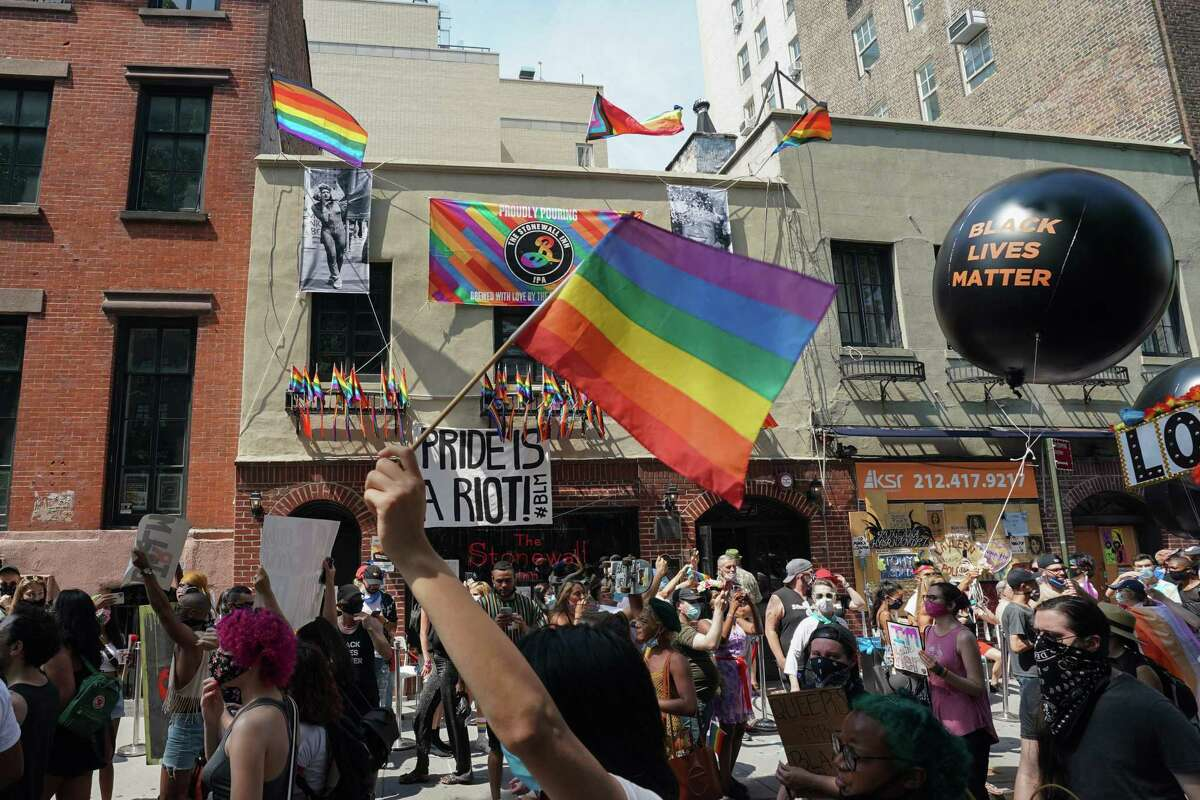 Protesters carrying signs walk past the Stonewall Inn during the Queer Liberation March hosted by The Reclaim Pride Coalition for Trans and Queer black lives and against police brutality in lower Manhattan on June 28, 2020 in New York. (Photo by Bryan R. Smith / AFP) (Photo by BRYAN R. SMITH/AFP via Getty Images)