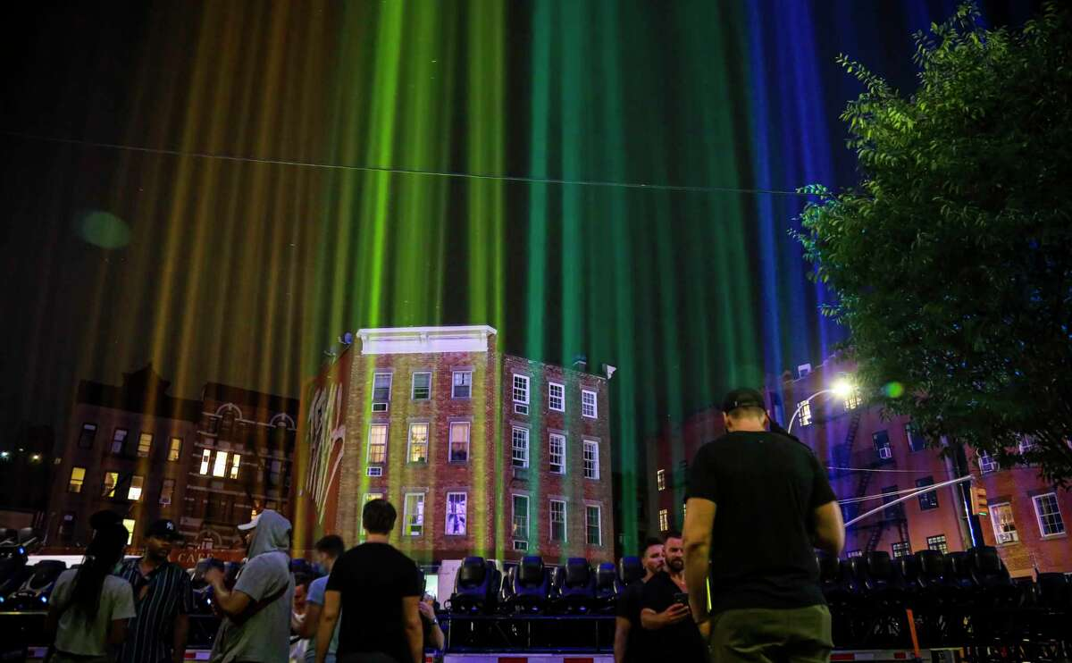 A rainbow light display illuminates the night sky in the West Village near The Stonewall Inn, birthplace of the gay rights movement, Saturday, June 27, 2020, in New York. The light installation was presented by Kind snack foods to mark what would have been the 50th anniversary of the NYC Pride March, which is canceled this year because of the coronavirus pandemic. (AP Photo/Bebeto Matthews)