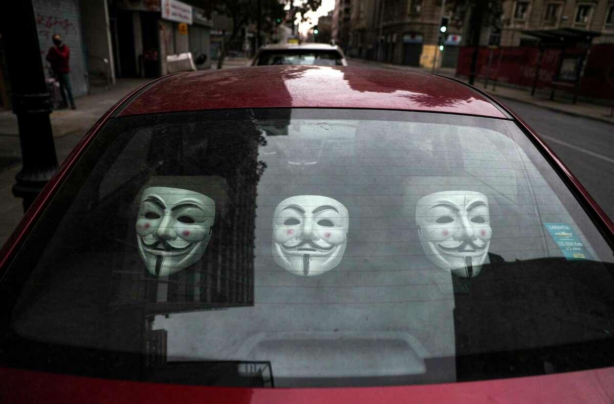 Guy Fawkes masks sit inside a car parked on a street in downtown Santiago, Chile, Sunday, June 28, 2020. (AP Photo/Esteban Felix)