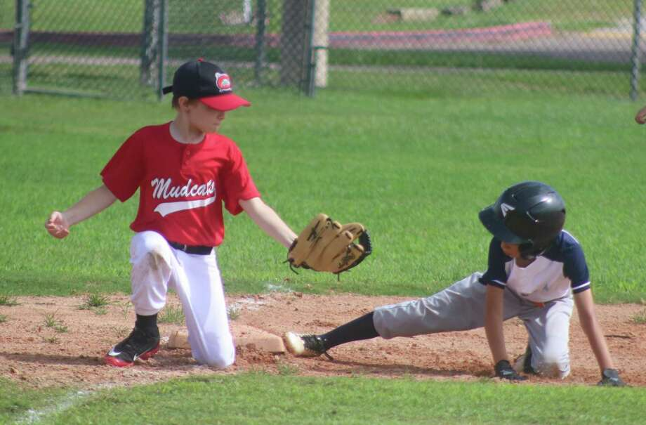 A Blue Astro slides into third base just ahead of the tag attempt during Sunday morning's game at the Chester E. Davis Sportsplex. Photo: Robert Avery