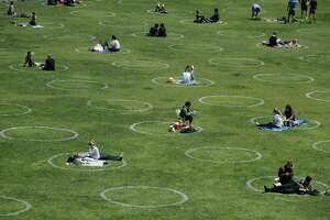 Visitors set up inside circles designed to help prevent the spread of the coronavirus by encouraging social distancing, at Dolores Park in San Francisco, Sunday, June 28, 2020.