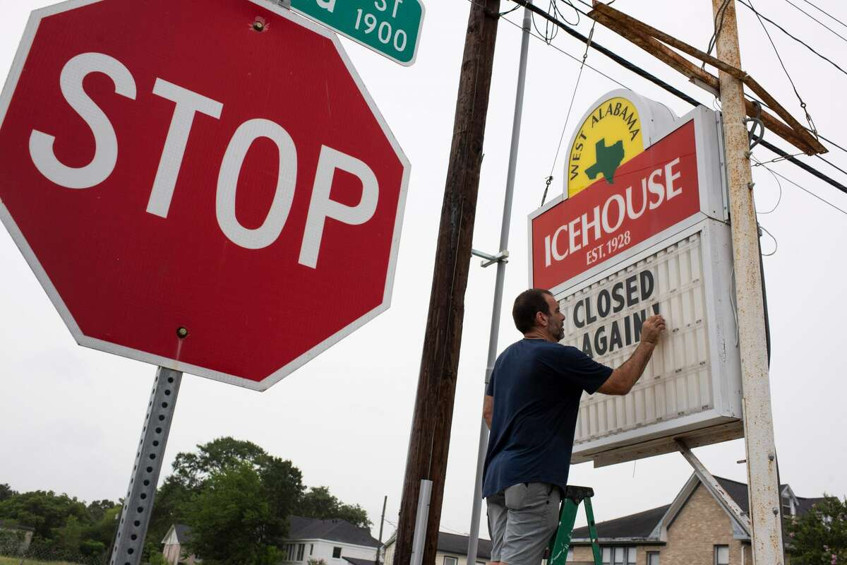 """Bar owner Petros J Markantonis changes the marquee outside his bar to """"Closed Again"""" at the West Alabama Ice House in Houston, Texas on June 26, 2020."""