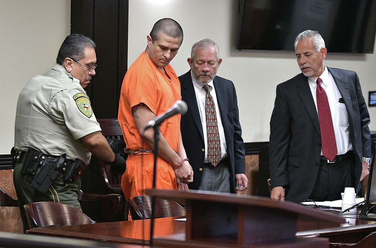 In this file photo, defense attorneys look on as alleged serial killer, former Border Patrol agent Juan David Ortiz, is escorted in the 406th District Courtroom at the Webb County Justice Center on Oct. 3, 2019. Ortiz is charged with capital murder of multiple persons, aggravated assault with a deadly weapon, unlawful restrain to substantial risk of injury and evading arrest.