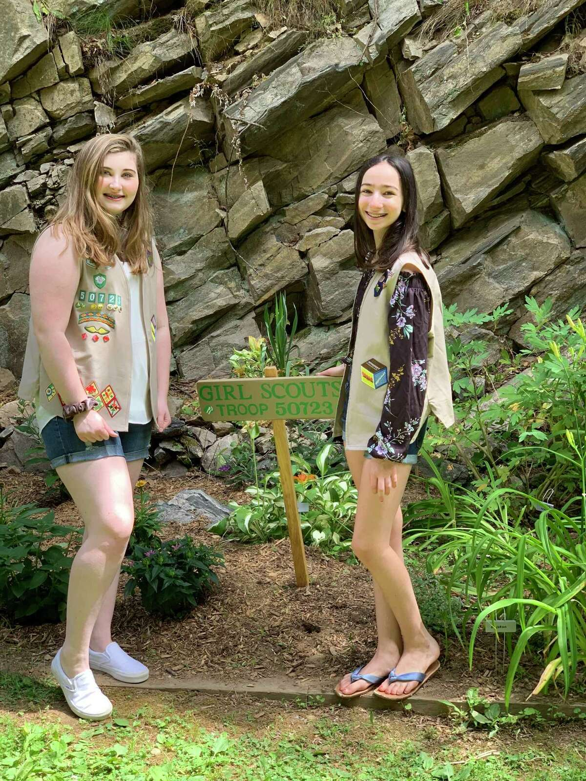Saint Mary Ridgefield Troop 50723 Girl Scouts Julia Jamba and Isabella Raduazzo stand in front of the pollinator garden they installed at Congregate Housing Prospect Ridge, RHA.