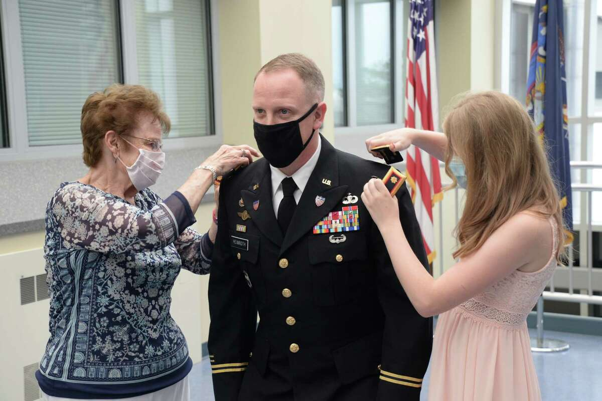 Grandmother Sally Heimroth and daughter Shayna Heimroth pin liutenant colonel insignias on Josh Heimroth during a promotion a ceremony at the New York National Guarda€™s Joint Force Headquarters, Latham. (Ryan Campbell / New York Army National Guard)