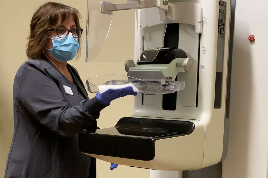 A mammography technologist from Solis Mammography, a department of HCA Houston Healthcare Conroe sanitizes the SmartCurve™ 3D mammography unit before and after examining each patient. Photo: Photo Courtesy HCA Houston Healthcare Conroe