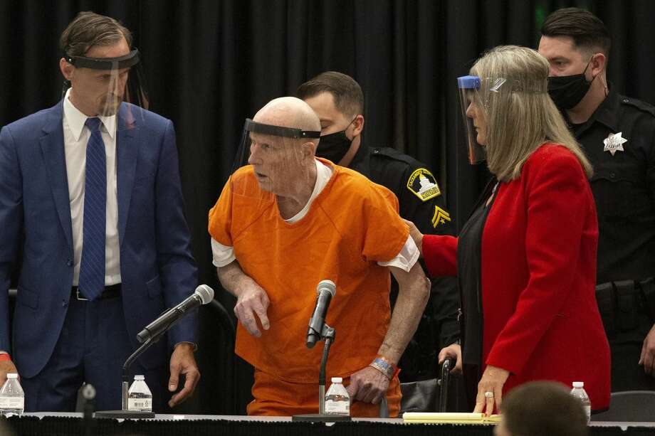 Joseph James DeAngelo, center, charged with being the Golden State Killer, his helped up by his attorney, Diane Howard, as Sacramento Superior Court Judge Michael Bowman enters the courtroom in Sacramento, Calif. Monday June 29, 2020. DeAngelo, 74, is expected to plead guilty 40 years after a sadistic series of assaults and slayings in California. Due to the large numbers of people attending, the hearing was held at a ballroom at California State University, Sacramento to allow for social distancing. (AP Photo/Rich Pedroncelli) Photo: Rich Pedroncelli/Associated Press / Copyright 2020 The Associated Press. All rights reserved