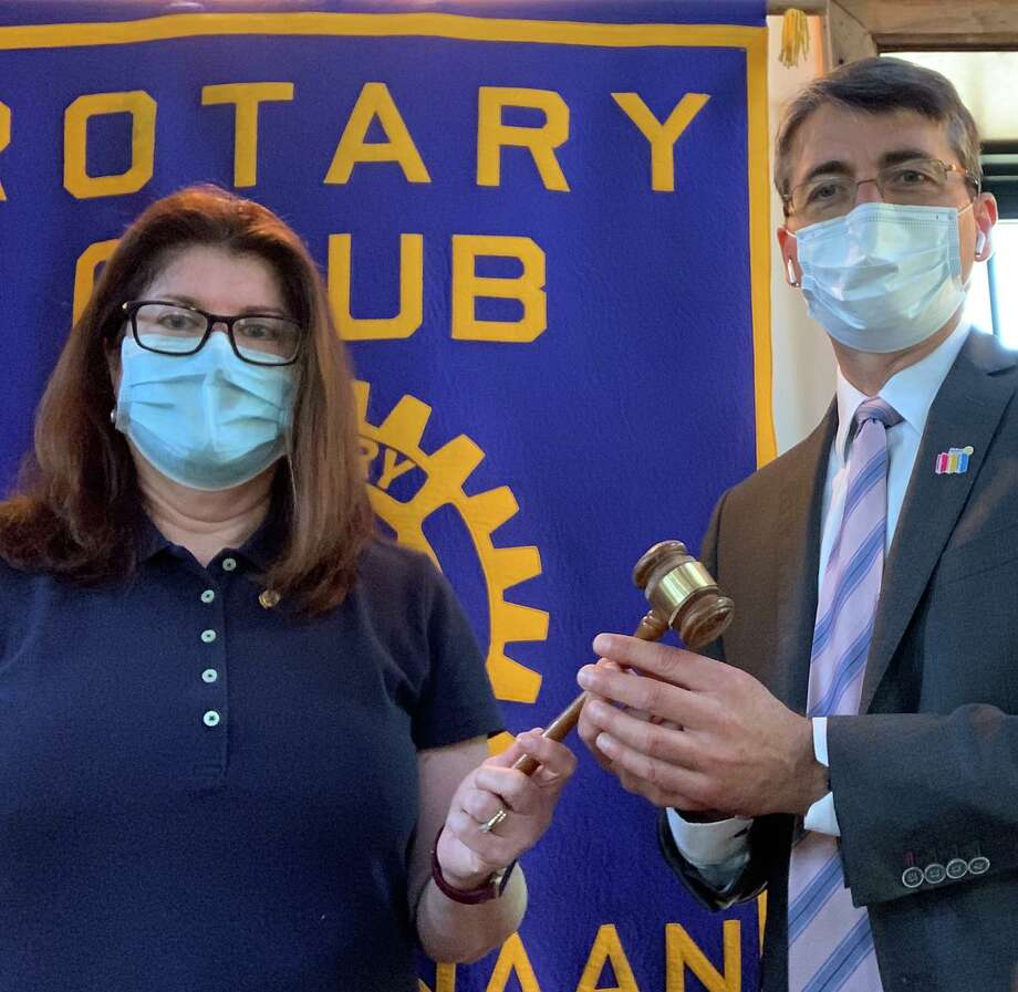Incoming President Alex Grantcharov receiving the ceremonial gavel from outgoing President Ann Dutille Cheney. Photo: Rotary Club Of New Canaan