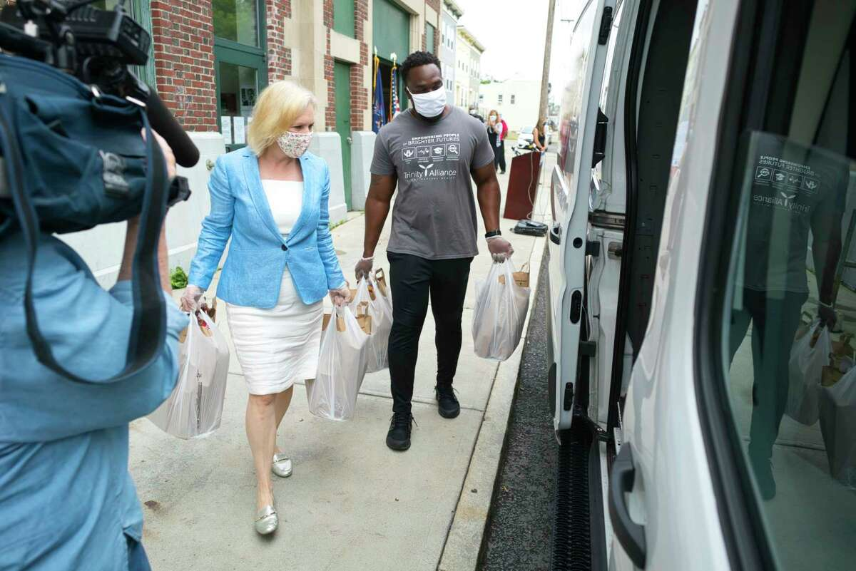 Senator Kirsten Gillibrand helps Andre Lewis, program manager for the Resource Center and the Food Pantry at the Arbor Hill Center of the Trinity Alliance of the Capital Region, pack and load food bags that will be delivered to homes on Monday, June 29, 2020, in Albany, N.Y. (Paul Buckowski/Times Union)