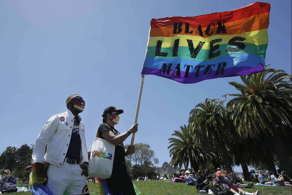 """Erik Webb, left, and Lance Toma wear rainbow face masks as Toma holds up a flag that reads """"Black Lives Matter,"""" at Dolores Park in San Francisco, Sunday, June 28, 2020, during a gay activists and supporters protest calling for an end to racial injustice and for police accountability. (AP Photo/Jeff Chiu)"""