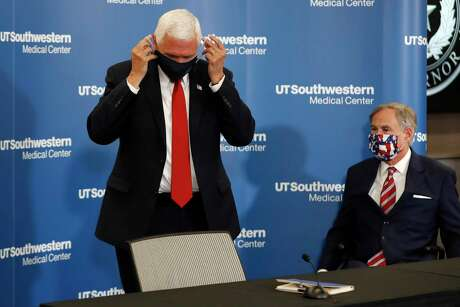 Vice President Mike Pence adjusts his mask as he and Texas Gov. Greg Abbott prepare to depart a news conference after Pence met with Abbott and members of his healthcare team regarding COVID-19 at the University of Texas Southwestern Medical Center West Campus in Dallas, Sunday, June 28, 2020.