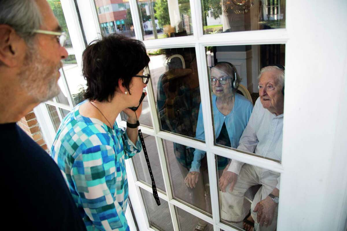 June and Doyce Spears look out a Silverado Hermann Park Memory Care Community window during a visit with their daughter Cara Barer and her husband Jorge Barer.