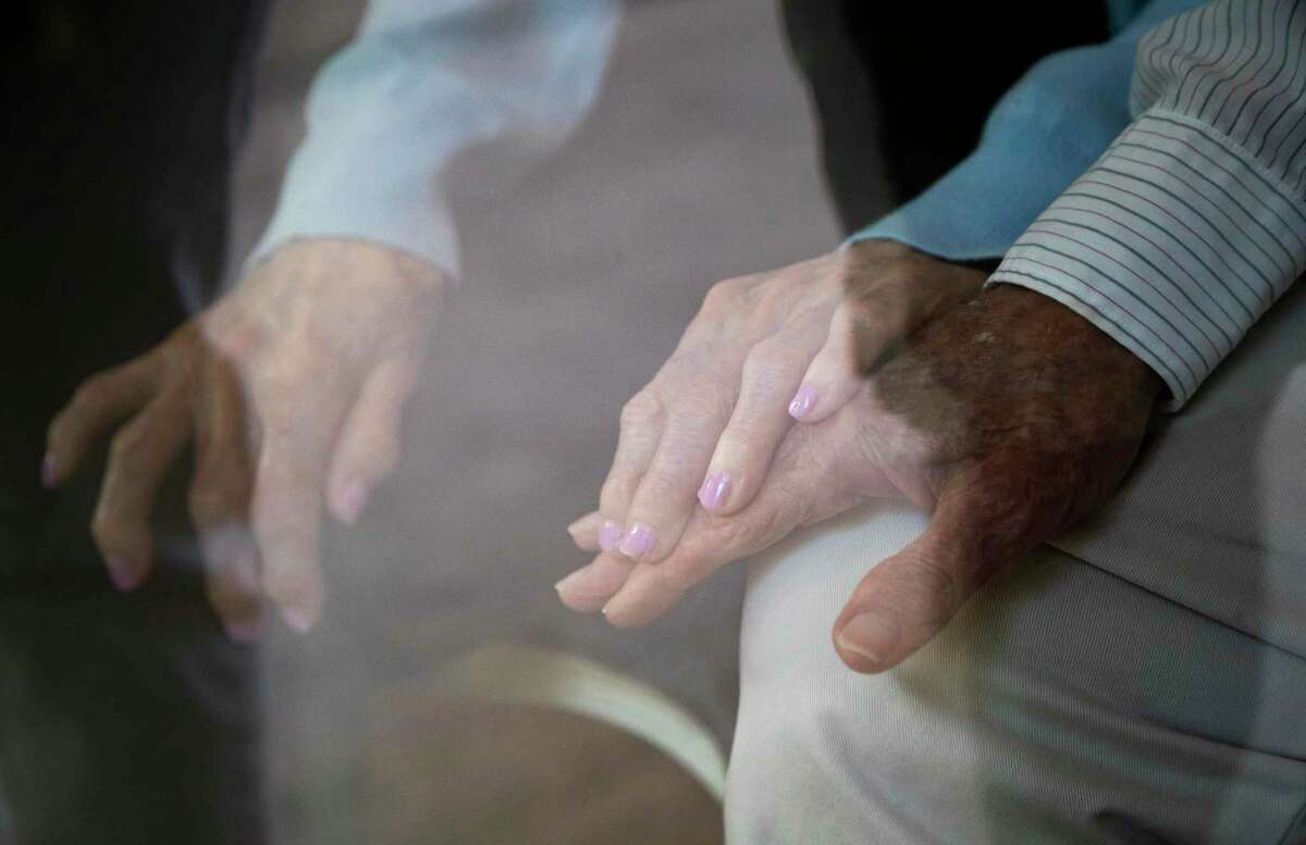 June Spears, 88, holds the hand of her husband Doyce Spears, 92, at Silverado Hermann Park Memory Care Community during a visit with their daughter Cara Barer and her husband Jorge Barer on June 19, 2020.