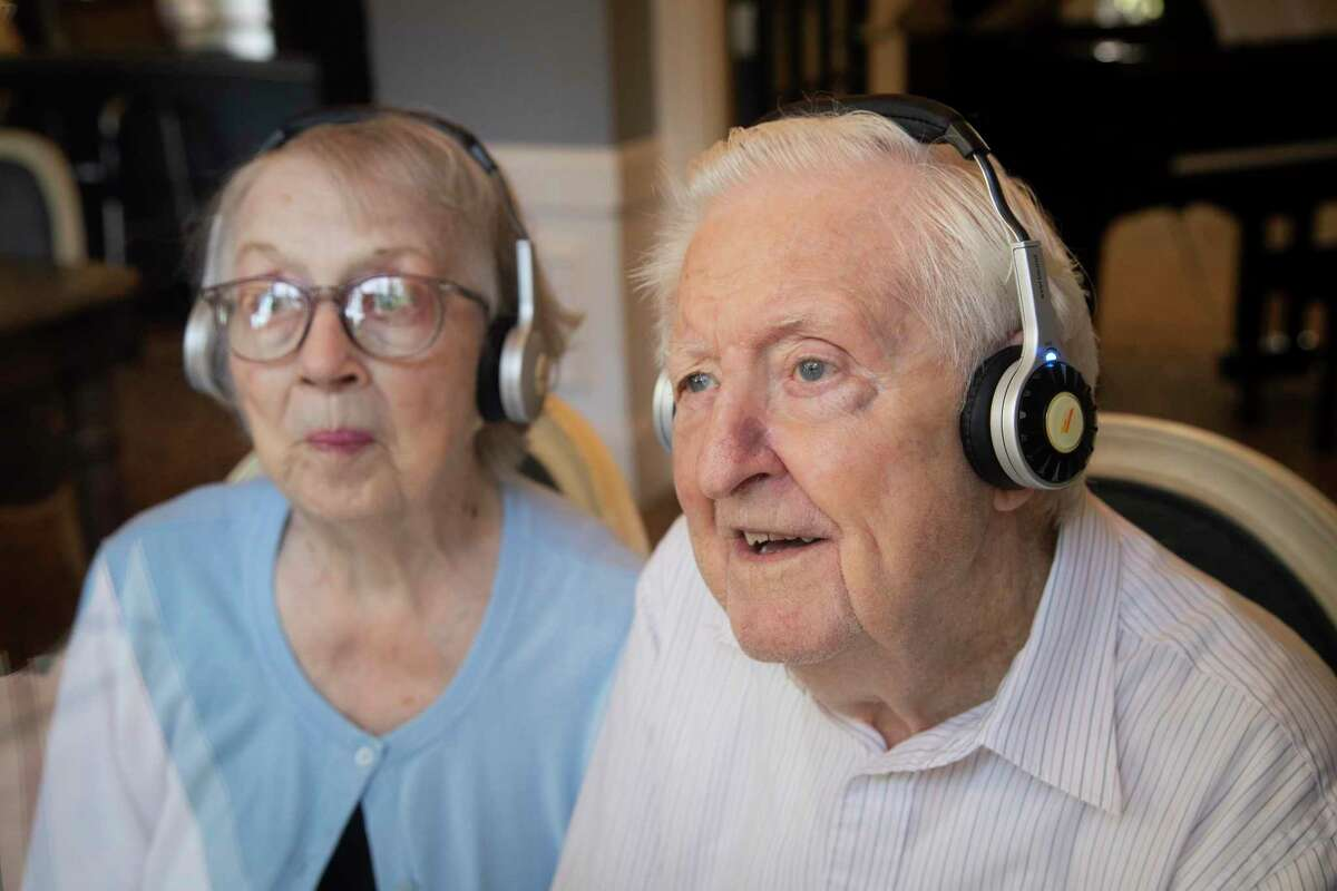 June Spears, 88, and her husband Doyce Spears, 92, wear headphones to speak through a window at Silverado Hermann Park Memory Care Community.