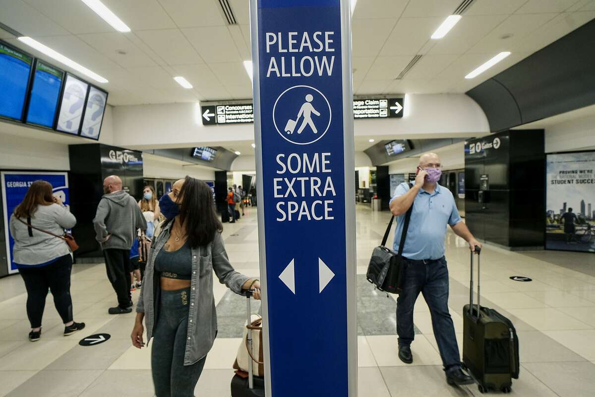 Travelers wearing protective masks pass in front of a sign notifying people to social distance at the Hartsfield Jackson Atlanta International Airport in Atlanta, Georgia, U.S., on Thursday, June 4, 2020. Airline stocks surged on Friday after carriers rushed to add flights for July. Photographer: SandyHuffaker/Bloomberg