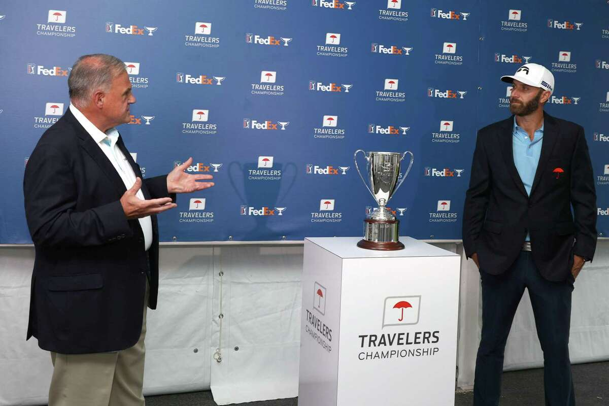 Dustin Johnson is presented with the trophy after winning the Travelers Championship Sunday in Cromwell.