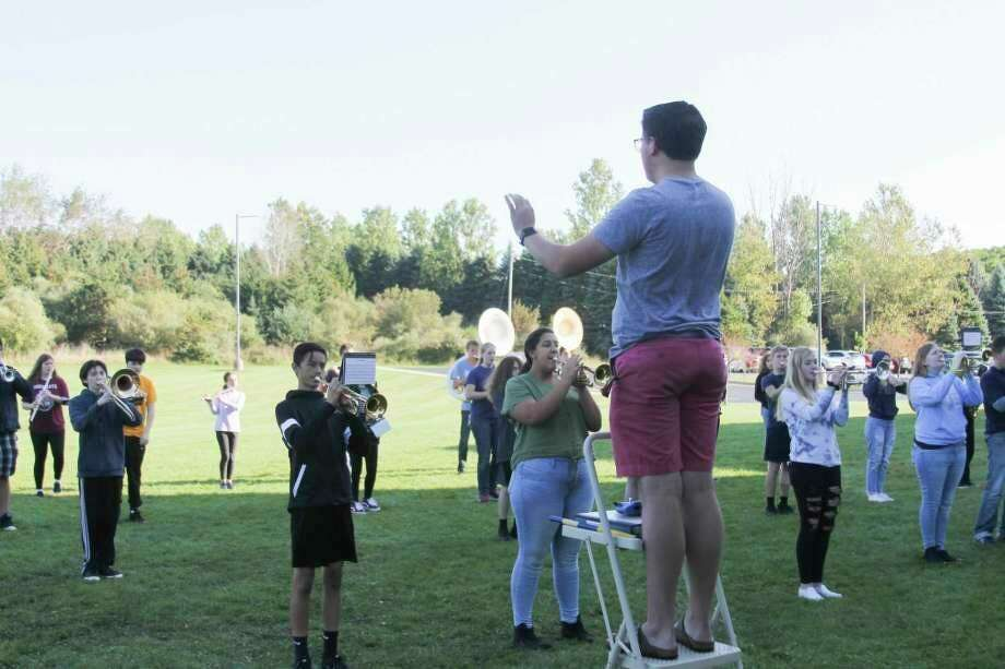 Student director Ryan Biller leads the Manistee High School Marching Band in a practice session for the Cadillac Marching Band Exhibition in September 2019. School band directors from the area are joining others from around the state in watching what guidelines might be put in place for the 2020-21 school year. It might include social distancing guidelines that might even send some groups outside to practice in the good weather. (File photo)