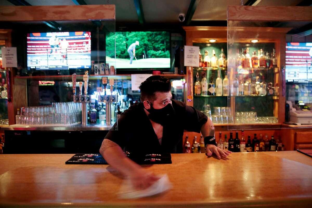 Manager Kevin Lemus cleans the bar at the Hideaway bar in Petaluma, California, Saturday, June 27, 2020.