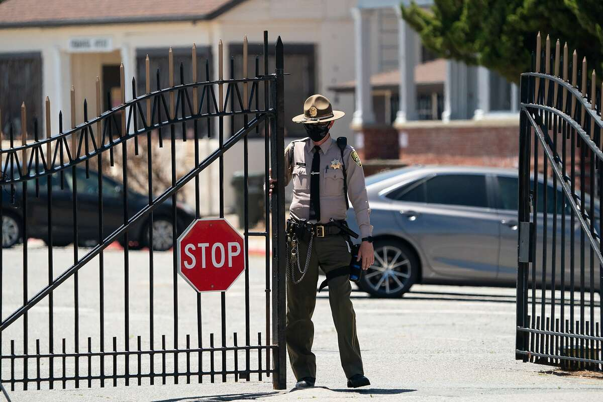 A guard closes the gates at San Quentin during the Stop San Quentin Outbreak rally on Sunday, June 28, 2020 in San Rafael, Calif.