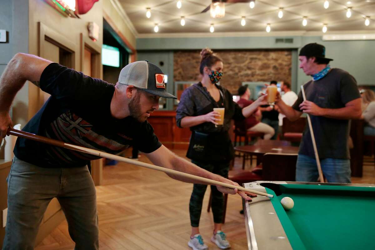 Roommates Brennan Kunkel, left, and Jo Nickerson (correct spelling) drink and play pool at McNear's Saloon and Dining House in Petaluma, California, Saturday, June 27, 2020. in Petaluma, California, Saturday, June 27, 2020.