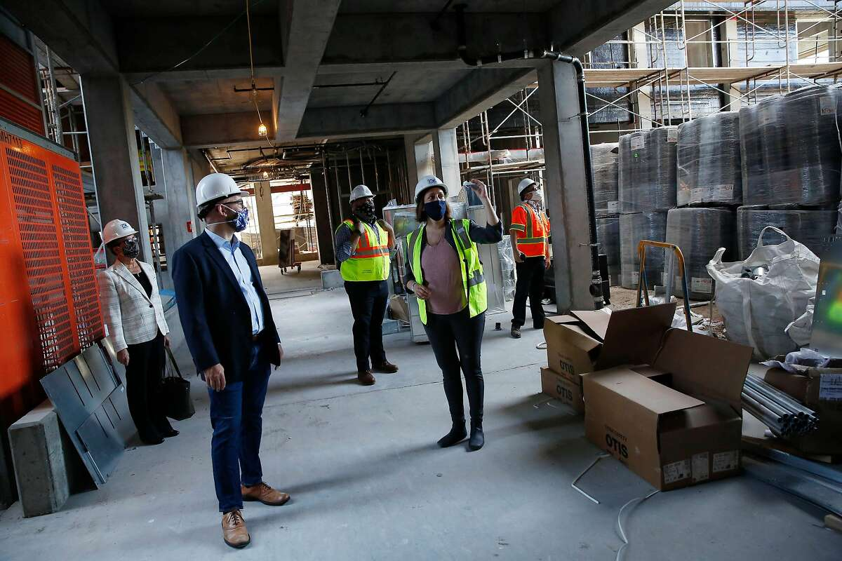 Mary Telling (second from right), Mithun project manager, talks with Supervisor Rafael Mandelman (second from left) while leading a short tour along with Deborah Raphael (left), director of San Francisco Department of Environment; Rommel Taylor (center); construction representative for Mayor's Office of Housing and Community Development; and Brendan Dwyer (right), construction representative for Mayor's Office of Housing and Community Development. Telling took them on a short tour of Casa Adelante at 2060 Folsom Street on Monday, June 29, 2020 in San Francisco, Calif.