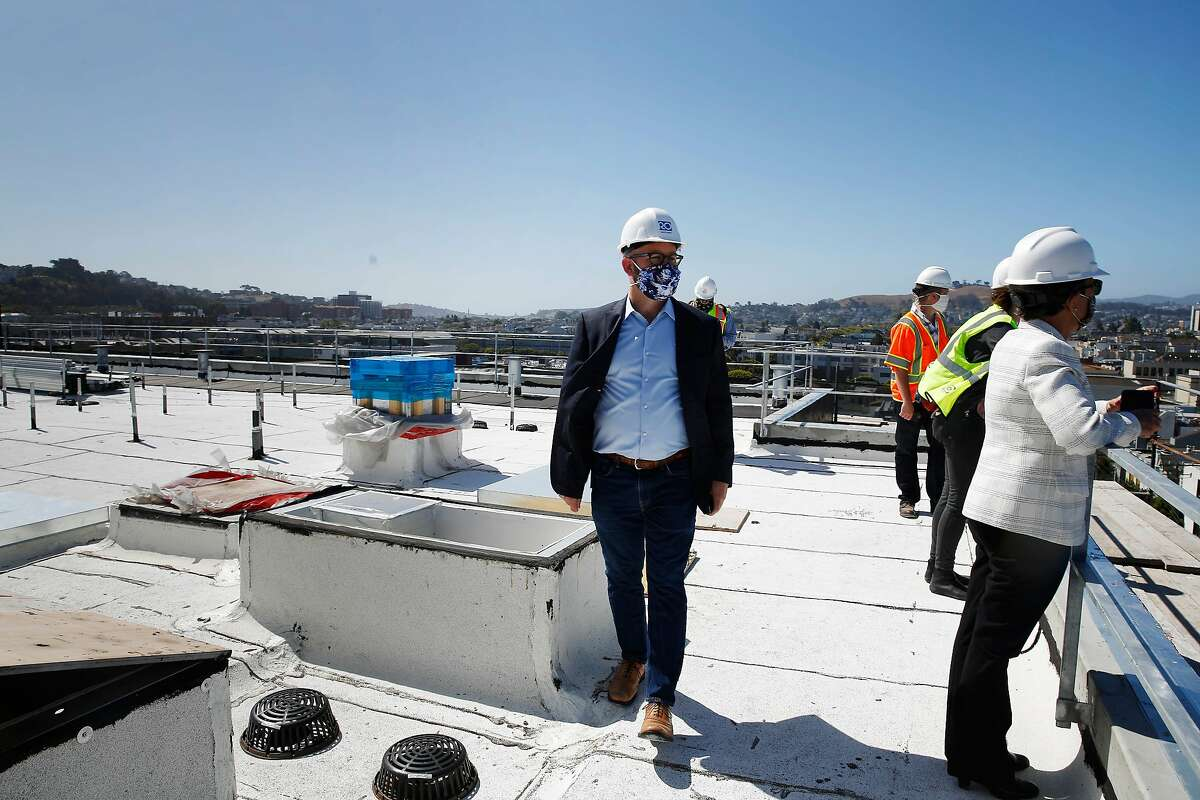 Supervisor Rafael Mandelman (left) walks across the roof of Casa Adalante at 2060 Folsom Street during a short tour on Monday, June 29, 2020 in San Francisco, Calif. Stanchions which will support the solar panel grid for Casa Adalante after they are installed are seen on left.