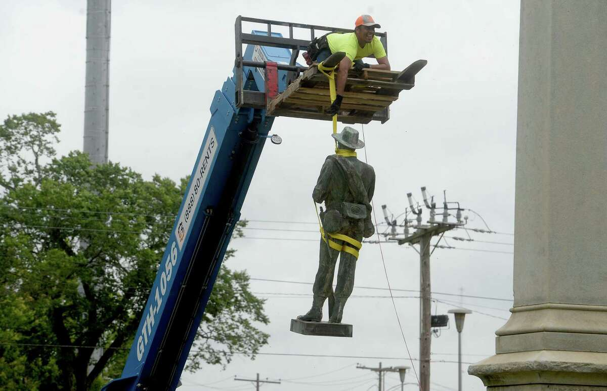 Workers with the City of Beaumont and Marsh Waterproofing, Inc., which does restoration work, dismantle and remove the Confederate monument in Wiess Park Monday, taking it apart piece by piece beginning with the soldier standing at the top. The city moved swiftly to remove the monument following last Tuesday's city council approval. Photo taken Monday, June 29, 2020 Kim Brent/The Enterprise