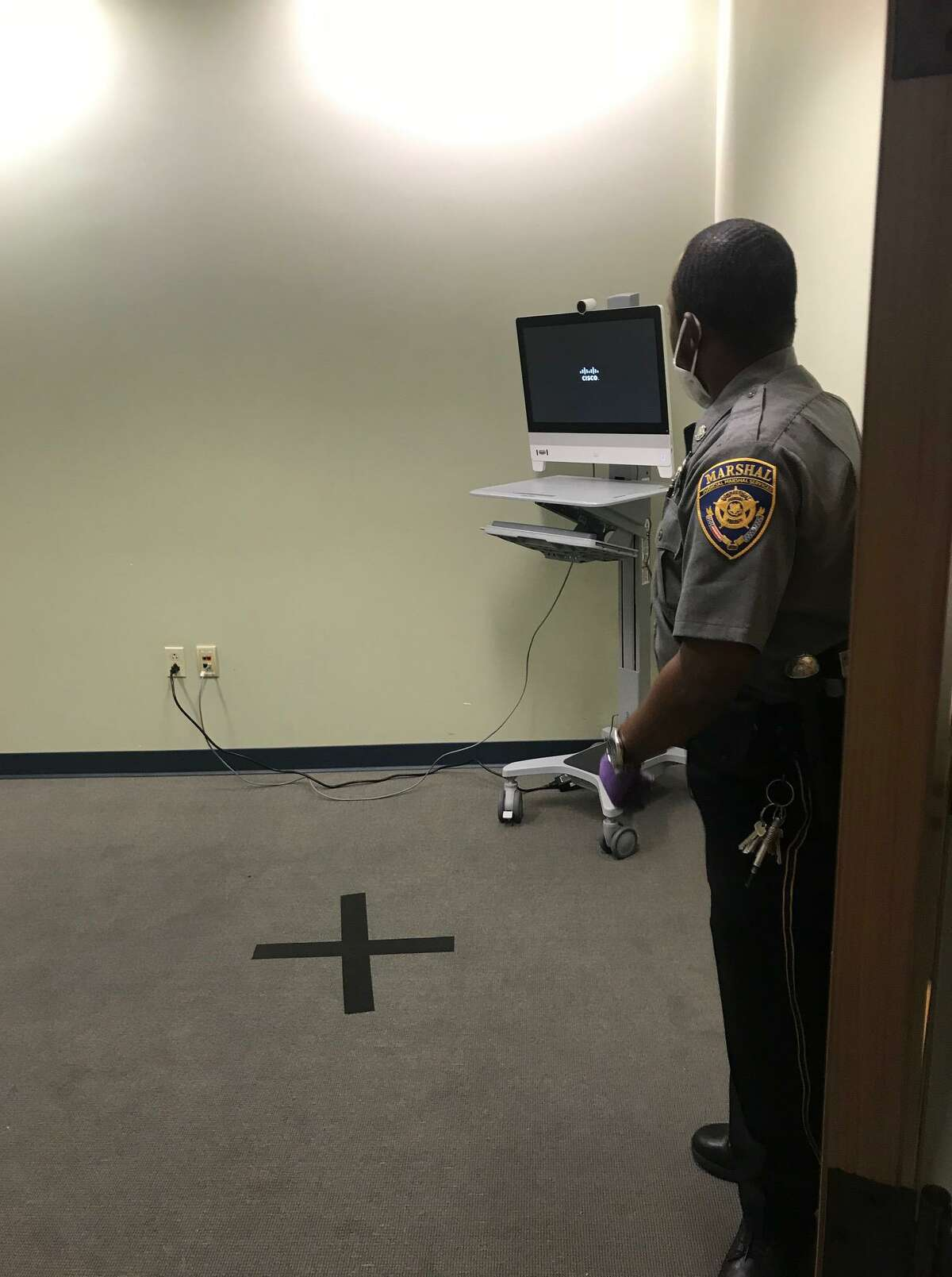 Judicial Marshal Jason Walker standing next to a monitor where defendants are arraigned via video camera at the Stamford courthouse on Monday. The X on the floor marks where attorneys and defendants are supposed to stand while on video.